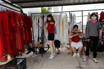 Woman selects outfits for photoshoots at a photo booth near Erhai Lake in Dali