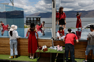 Tourists pose for photos on a mirror platform at a photo booth near Erhai Lake in Dali