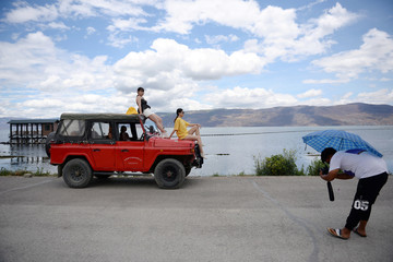 Women sit atop a vehicle as they pose for photos during a photoshoot session near Erhai Lake in Dali