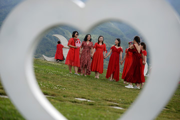 Women posing for pictures are seen through a heart-shaped prop near Erhai Lake in Dali