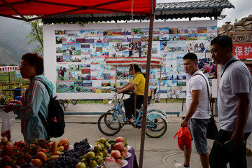 People walk past a board showing tourists' photos taken inside an attraction, in front of a fruit stall near Erhai Lake in Dali