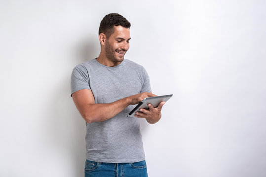 Happy man standing with ipad looking at the screen of it.- Image