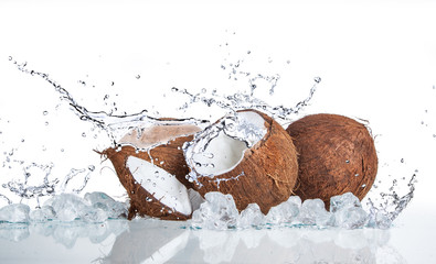 tropical coconut with ice and splashing water on white background