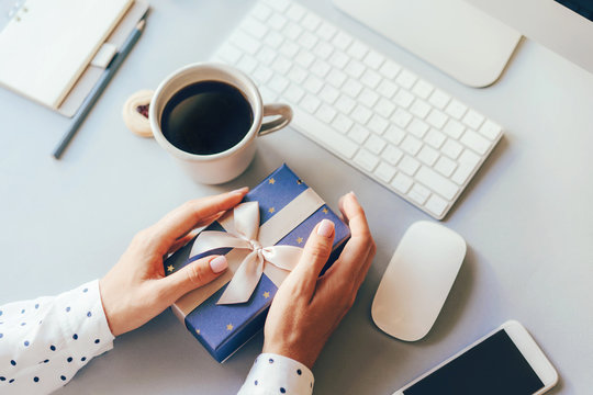Blue gift box decorated with a golden ribbon bow in female hands against the background of the office workplace, gift delivery, coffee break during office hours, corporate greetings and parties.