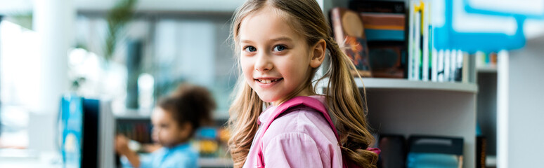 panoramic shot of cheerful kid with pink backpack standing in library