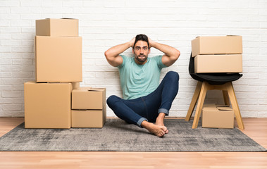 Handsome young man moving in new home among boxes with surprise facial expression Wall mural