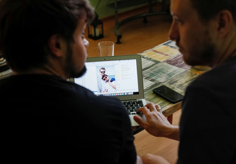 Gay married couple watches their wedding photos in their flat in Kiev