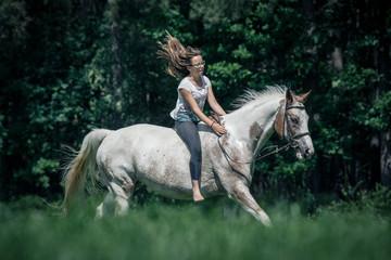 Ein Mädchen reitet ohne Sattel über die Wiese
