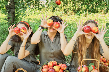Girls with Apple in the Apple Orchard. Beautiful sisters with Organic Apple in the Orchard. Harvest Concept. Garden, teenagers eating fruits at fall harvest. Wall mural