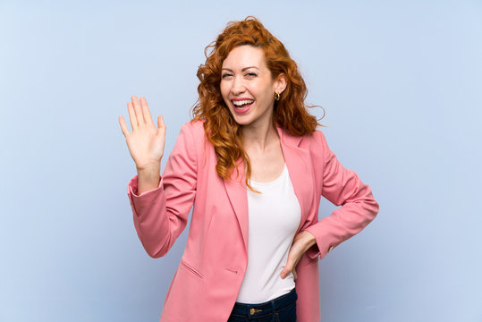 Redhead woman in suit over isolated blue wall saluting with hand with happy expression