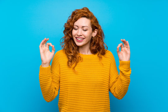 Redhead woman with yellow sweater in zen pose