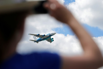 A visitor takes a picture of an Airbus A380 as it performs at the 53rd International Paris Air Show at Le Bourget Airport near Paris