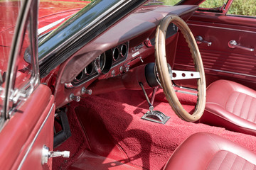Interior view with instruments and wooden steering wheel of an old red cabriolet