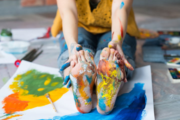 Art therapy. Cropped shot of artist sitting on floor, showing feet and hands dirty with multicolor paint. Blur background. Wall mural