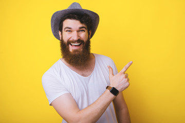 Young bearded man pointing aside on yellow background, copy space. Wall mural