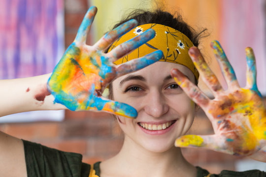 Art therapy. Closeup portrait of young female artist having fun in studio, smiling, showing hands dirty with paint.