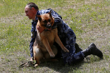 An officer holds a German shepherd dog during the annual cynologist competition for teams of the Federal Penitentiary Service, outside Krasnoyarsk