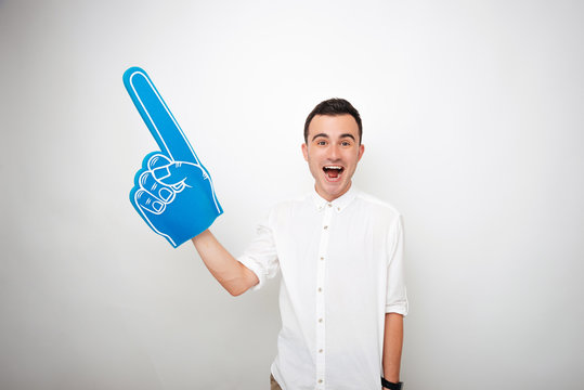 Young cheerful man in white on white background is excited and holding a fan foam finger hand. Cheering up. Number one.