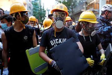 Protesters protect themselves with helmets, masks and foam pads during a demonstration demanding Hong Kong's leaders to step down and withdraw the extradition bill, in Hong Kong