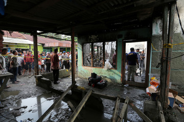 Locals look at a house, used as a factory producing matchsticks, after a fire swept through, at Binjai district in Langkat, North Sumatra province