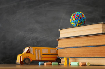 education and back to school concept. cardboard bus, books and chalks in front of classroom blackboard