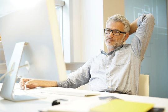 Relaxed businessman sitting at desk with arms behind head