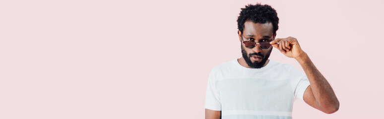 handsome african american of man in sunglasses isolated on pink