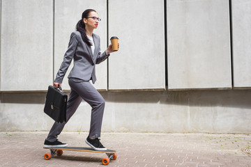 calm businesswoman in formal wear riding on skateboard, holding paper cup and briefcase in hands
