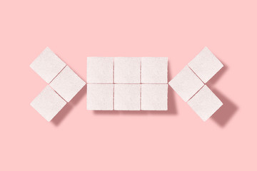 candy made of white cubes of sugar on a pink background