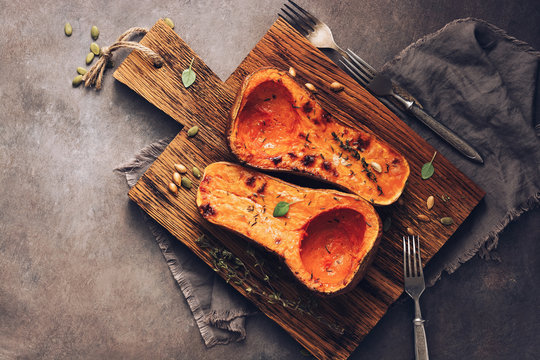 Delicious baked or butternut squash pumpkin with thyme on a cutting board, dark rustic background. Top view, flat lay. The concept of diet nutrition.