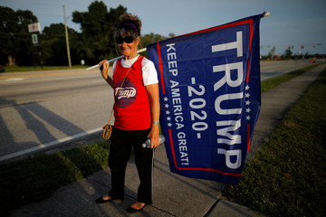 Robin Mayo holds a Trump flag during a sign waving rally in Clearwater