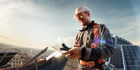 Fototapeta Solar energy engineer using tablet for check power station smiling in roof obraz