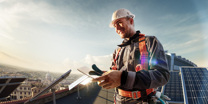 Solar energy engineer using tablet for check power station smiling in roof