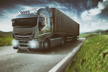Grey truck moving fast on the road in a natural landscape with cloudy sky Wall mural