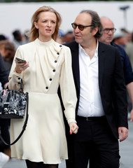 Xavier Niel, founder of French broadband Internet provider Iliad and his partner Delphine Arnault leave during Men's Fashion Week in Paris