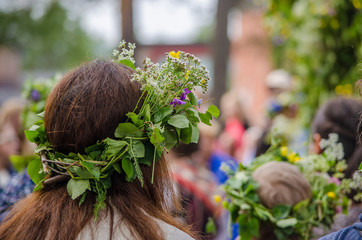 Woman enjoying swedish traditional mid summerday in a sunny day with colourful flower crown