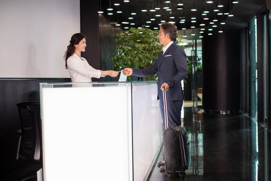 Receptionist giving business card to businessman