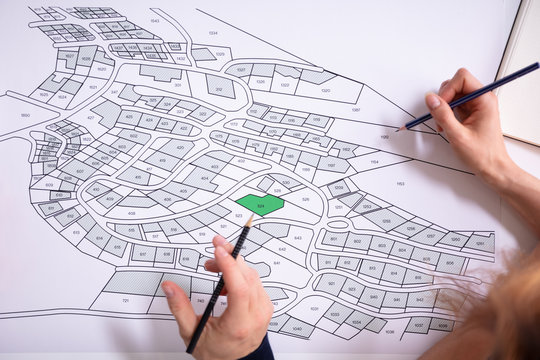 Human Hand Holding Pencil Over Cadastre Map