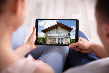Couple Looking At House On Tablet Fototapete
