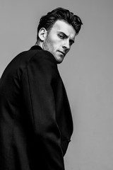 Portrait of young and handsome model with a strong look in a classic black style clothing. Studio shot. Copy space.
