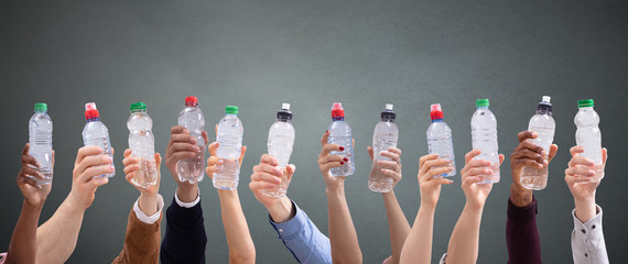 Different People Holding Water Bottles In A Row