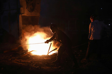 Workers melt metal scraps in the furnace of a steel mill to produce rods in Dhaka