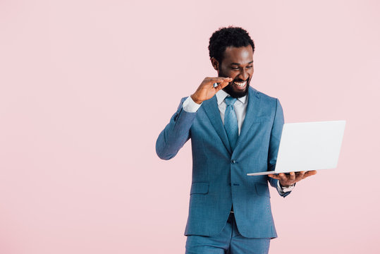 happy african american businessman having video chat on laptop isolated on pink