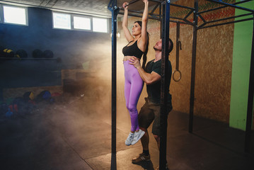Beautiful strong muscular woman doing pull up exercise with help of personal trainer it the gym.