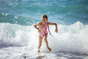 Happy young girl playing on beach and running away from big waves
