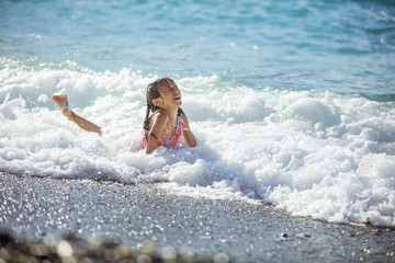 Happy young girl playing in waves on beach