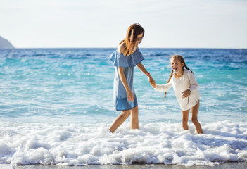 Young woman and her daughter enjoying summer day on beach