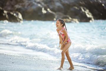 Happy girl playing on beach