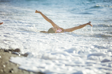 Young girl playing in breaking waves on beach