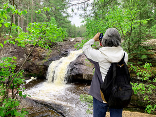 Woman tourist taking waterfall pictures